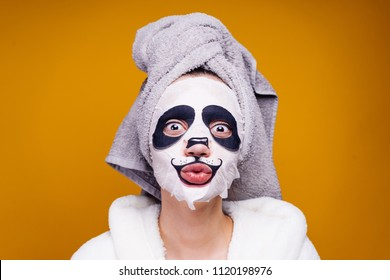 funny young girl with a towel on her head posing, on her face a moisturizing mask with a panda face