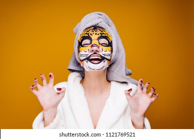 a funny young girl in a white coat and with a towel on her head growls, on her face a moisturizing mask with a leopard face
