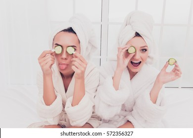 Funny young girls in bathrobes making mask with cucumber and having fun.