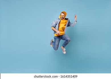 Funny young hipster guy in fashion jeans denim clothes posing isolated on pastel blue background studio portrait. People emotions lifestyle concept. Mock up copy space. Jumping like playing guitar