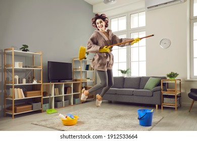 Funny young housewife cleaning house, fooling around and having fun. Happy beautiful woman in hair curlers and face mask tidying up her home, jumping, singing songs and playing on pretend mop guitar