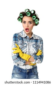 Funny young housewife with hair rollers and rubber gloves on white background
