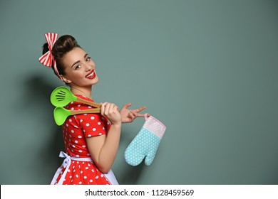 Funny young housewife with oven mitten and cooking utensils on color background