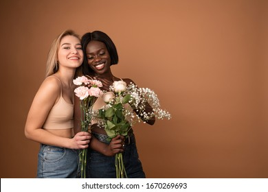Funny young lesbian couple two international girls in casual outfit celebrating isolated on pastel orange background with copyspace. Valentine's Day Women's Day birthday holiday concept. Holding