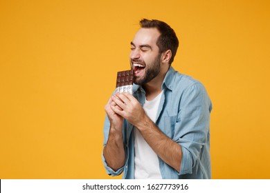 Funny young man in casual blue shirt posing isolated on yellow orange wall background, studio portrait. People sincere emotions lifestyle concept. Mock up copy space. Holding, biting chocolate bar