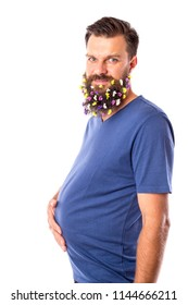 Funny young man with flowers in his beard holding hand on the belly over white