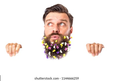 Funny young man with flowers in his beard looking up over white