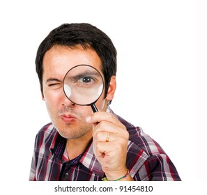 Funny young man looking through magnifying glass, isolated on white