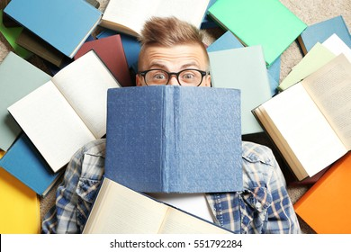Funny young man lying on floor among books