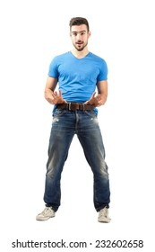 Funny young man pulling his belt. Full body length isolated over white background.