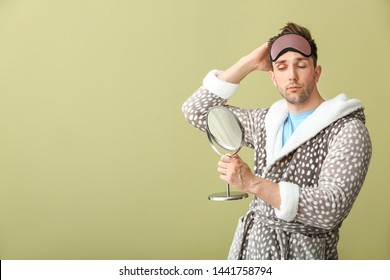 Funny young man with sleep mask and mirror on color background