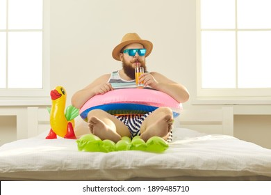 Funny young man in sunglasses and summer wear sipping beach cocktail, sitting barefoot in inflatable lifebuoy at home. Covid-19 quarantine, vacation in lockdown, canceled holiday travel plans concept