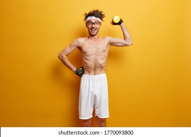 Funny young man with very thin body, trains muscles and lifts dumbbell, looks at camera with happiness, wears sport gloves and white shorts, stands against vivid yellow background, enjoys workout