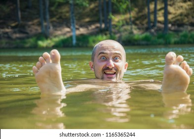 Funny young man in the water with his feet up,  rest outdoor swimming in the lake in the forest