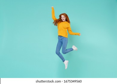 Funny young redhead woman girl in yellow knitted sweater posing isolated on blue turquoise background studio portrait. People emotions lifestyle concept. Mock up copy space. Jumping, spreading hands