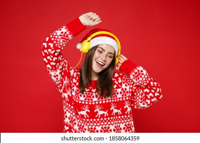 Funny young Santa woman 20s in sweater Christmas hat listening music with headphones dancing rising hands isolated on red background studio portrait. Happy New Year celebration merry holiday concept