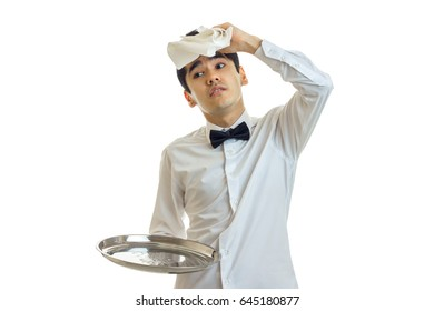 funny young waiter's shirt keeps empty tray and applies the napkin to head