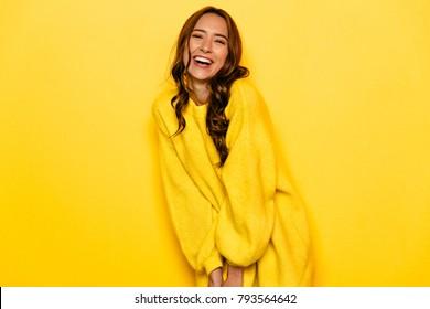 Funny junge Frau mit lockigem Haar in gelbem Pullover, weithin lächelnd, Einzeln auf gelbem Hintergrund.