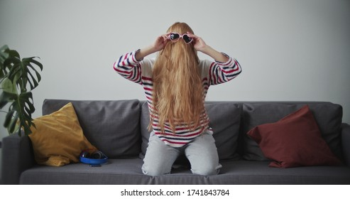 Funny young woman having fun on sofa in morning. Attractive red girl in cheerful mood . Female model in home clothes waving her hair and wearing sunglasses.