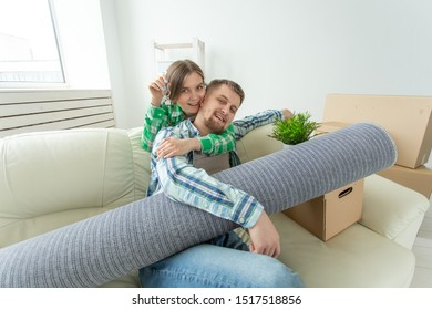 Funny young woman and her husband holding in hands the keys to their new apartment while sitting in her new living room. Housewarming and mortgage in new building concept