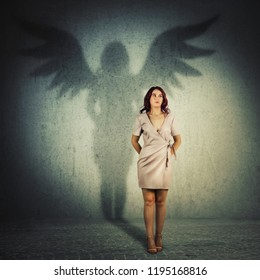 Funny young woman hiding hands behind her back looking away. Full length female portrait casting a superhero shadow with angel wings on a dark room wall. Inner power, ambition and leadership concept.