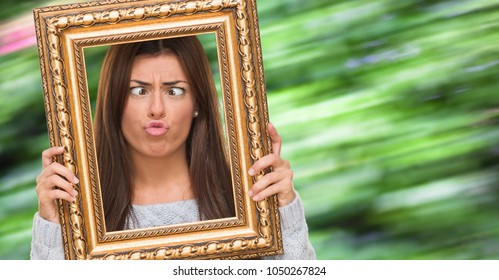 Funny Young Woman Holding Frame against a nature background