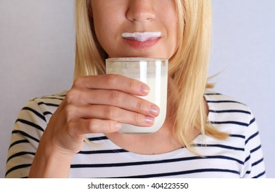 Funny young woman mustache from yogurt or milk. Dairy products concept