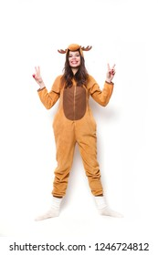 Funny young woman in pajamas jumping and having fun on white background . Girl dressed in kigurumi costume deer