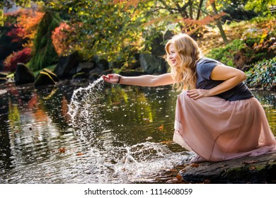 Funny young woman playing with water, sitting on a stone near the lake in autumn park