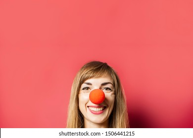 Funny young woman with a red nose of a clown on a pink background. Concept red nose day, holiday, party, clown