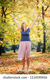 Funny young woman throw golden autumn leaves in the air. Vivid autumn