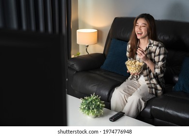funny young woman watching TV and eating popcorn on sofa at night