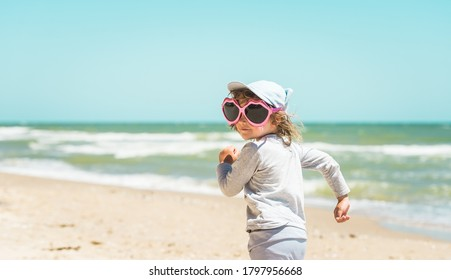 funnylittle girl in big sunglasses on the beach. Summer vacation and love. Sunglasses like red lips. Happy kid on the see beach. Stylish child running