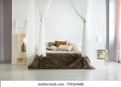 Fur brown bedding and glass lamp in minimalist comfy bedroom with natural interior design and bed canopy
