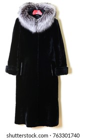 Fur coat black mute with fur collar of polar fox on wall background. Fur coat on hanger. Outerwear. Luxury fur coat.