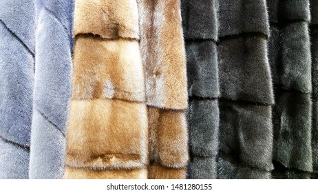 Fur coats in a row on a hanger in a store. Women's fashion, clothing from natural mink fur for sale in different colors