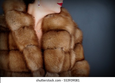 Fur texture close up. Woman in fur coat. Grey background