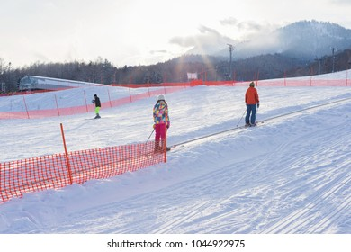 Furano, Japan - January 19, 2017: Unidentified skiiers moving on snow escalator with mountain and forest background in Furano, Hokkaido, Japan.