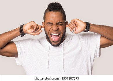 Furious african American millennial man isolated on grey studio background plug ears avoid loud disturbing noise, mad angry biracial male scream yell feel stressed annoyed by noisy sound