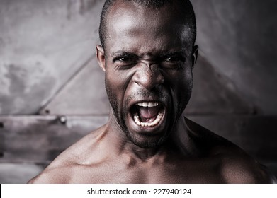 Furious and aggressive. Portrait of furious young shirtless African man shouting and looking at camera