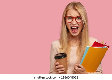 Furious blonde woman yells with madness, being discontent with exam results after long preparation, wears transparent glasses, drinks takeaway coffee, poses against pink background, copy space
