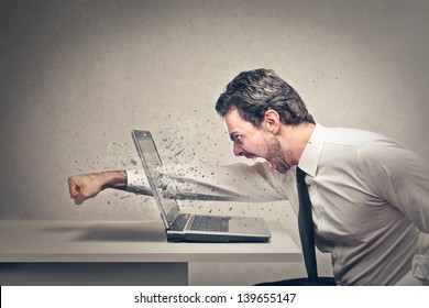furious businessman throws a punch into the computer