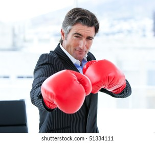 Furious businessman wearing boxing gloves in his office