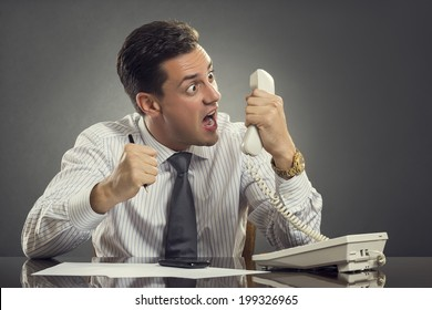Furious businessman in white shirt and necktie having an anger outburst during a phone conversation at work. Impulsive businessman yelling and showing an enraged face grimace during phone call.