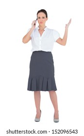 Furious businesswoman having a phone call while posing on white background