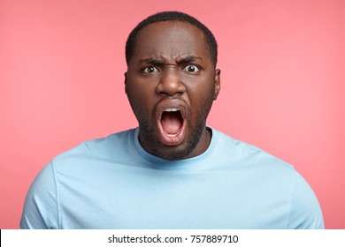 Furious dark skinned male screams loudly, annoyed with interlocutor, expresses negative emotions and feelings, keeps mouth widely opened. Angry African boss shouts at coworkers, being strict