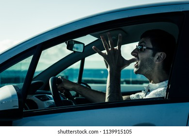 Furious driver gesticulates with open hand on white car. Desperate young man with sunglasses driving with anger. Upset, aggressive, impatient, bad manners concepts. Cold blue effect on sunny day
