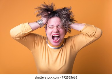 Furious and enraged young woman screaming with anger, yellow background