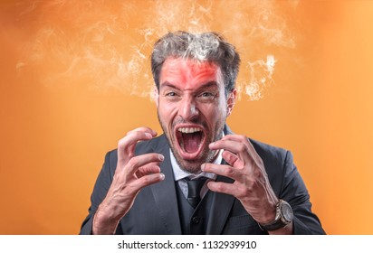 Furious and frustrated caucasian businessman steaming with rage, giving off smoke