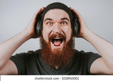 Furious handsome guy wearing trendy clothes enjoying his lovely sound tracks. Close up of handsome man screaming while listening to music. Happy amazed young bearded hipster man listen music.